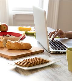 Eine Hand Tipps etwas auf eine Laptoptastatur ein und Frühstück steht auf dem massiven Holztisch