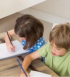 Kinder malen auf ein Blatt Papier an einem massiven Holztisch