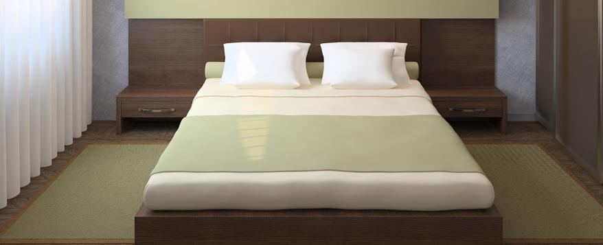 Edle Kombination: Designbett aus dunklem Holz mit passenden Nachtschränken und grünen Accessoires im angesagten Pastellton