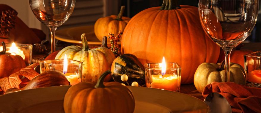 Kürbisse, Kerzen und warme Farben lassen den Esszimmertisch gemütlich und herbstlich wirken