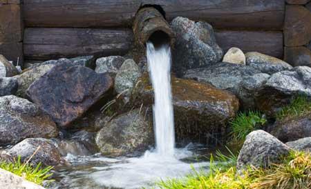 Ein plätschernder Brunnen aus Holz und Stein belebt den Bauerngarten