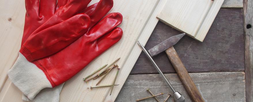 Zum Verlegen der Holzfliesen auf der Terrasse braucht man nur wenige Werkzeuge, zum Beispiel Hammer und Schraubenzieher